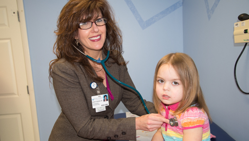 A female doctor uses a stehtoscope on a child